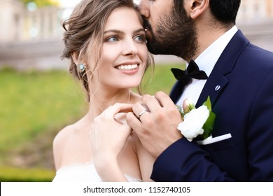 Handsome young groom kissing his happy bride outdoors