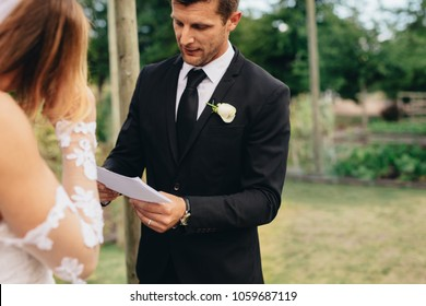 Handsome young groom reading wedding vows from a paper. Wedding ceremony rituals of a couple in park.