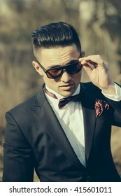 Handsome young groom in wedding suit with bow tie in sunglasses sunny day outdoor