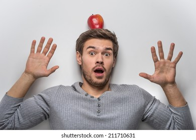Handsome young guy balancing red apple on his head. guy wearing grey sweater isolated on white background
