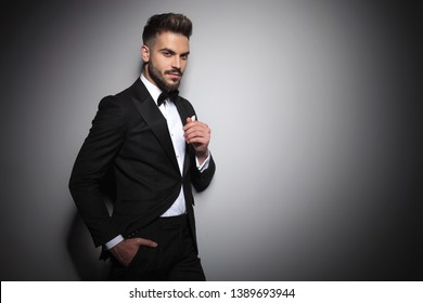 handsome young guy in black tuxedo holding hand in pocket on dramatic studio background