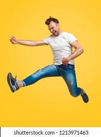 Handsome young guy in casual outfit screaming and pretending to play imaginary guitar while jumping in air on bright yellow background