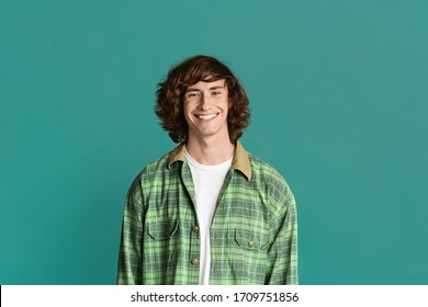Handsome young guy with curly hair smiling on color background