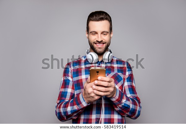 Handsome young guy with headphones and smartphone in hands choosing his favourite music track