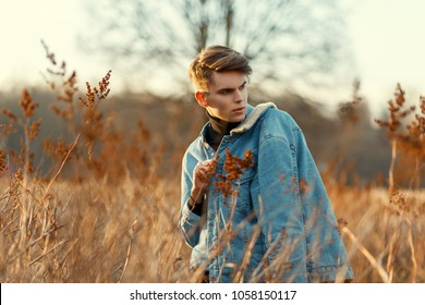 Handsome young guy with a jeans fashion jacket and denim shirt walking in a field with grass at sunset