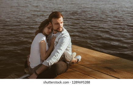 Handsome young guy looking away and hugging peacefully sleeping girlfriend while sitting on lumber pier near calm water