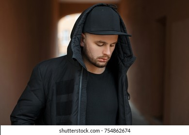 Handsome young guy model in a hood with a black stylish baseball cap and winter jacket posing on the street