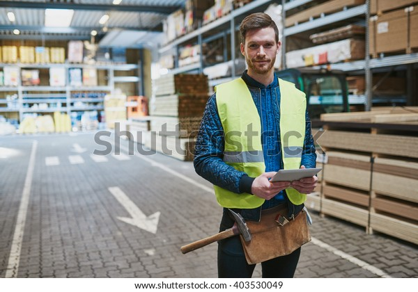 Handsome young handyman or warehouse supervisor standing amongst the building supplies with a tablet in his hand smiling at the camera