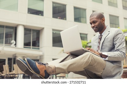 Handsome young happy businessman working on laptop outdoors on a background of corporate building. Instagram filter effect