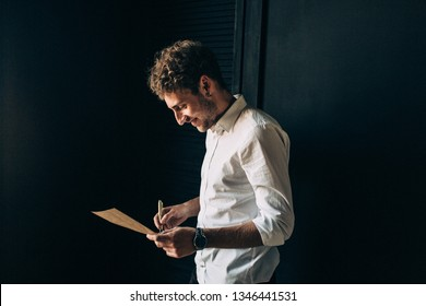 Handsome young happy men and groom reading a letter