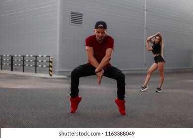 handsome young hip-hop man dancer in a red fashionable T-shirt, black jeans and a red shoes dancer in the street. Girl dancer on the background