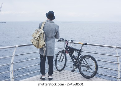 handsome young hipster guy in hat with bike looking at the sea wearing backpack on wood floor back view