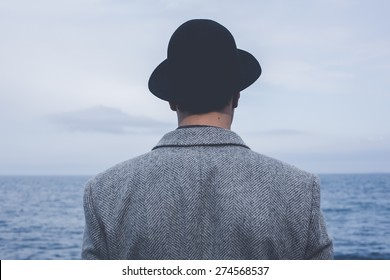 handsome young hipster guy in hat looking at hazy sunshine through a thick mist on a calm sea and blue skies back view
