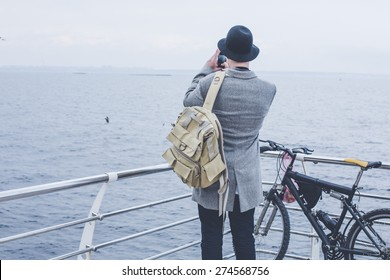 handsome young hipster guy in hat with bike taking picture of the sea with his smart phone wearing backpack on wood floor back view