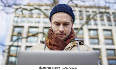 Handsome young hipster male using his laptop outdoors in teh city
