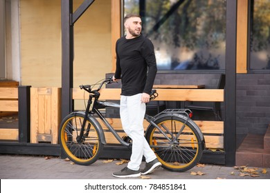 Handsome young hipster man with bicycle outdoors