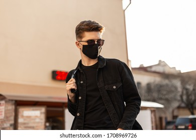 Handsome young hipster man with hairstyle in trendy sunglasses in fashionable black denim jacket in stylish medical black mask walks on street on sunny day. Attractive guy model. Fashion 2020. Spring.