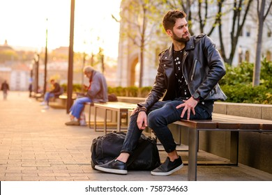A handsome young hipster man sitting and looking around on a bench in the sunset