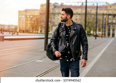 A handsome young hipster man walking next to a tramline and looking around