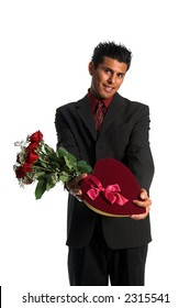 Handsome young Hispanic business man in a suit presenting a dozen red roses and a heart shaped box of candy