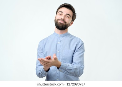 Handsome young hispanic man with beard in blue shirt applauding