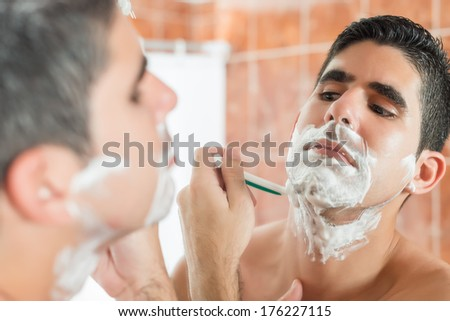 Handsome young hispanic man shaving in front of a mirror