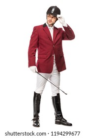 handsome young horseman in uniform holding horseman stick and looking away isolated on white
