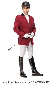 handsome young horseman in uniform holding horseman stick and looking at camera isolated on white