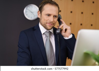 Handsome young hotel manager checking information on his desktop computer at the front reception desk as he listens to a call from a customer