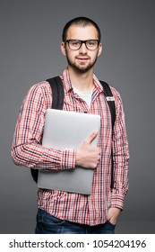 Handsome and young indian Male college student carrying bag on white background while holding college laptop