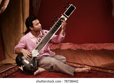 Handsome young Indian man plays a Sitar