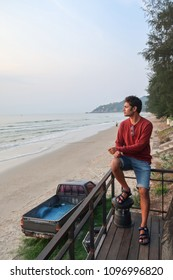 Handsome young indian man relaxing on terrace at sea beach