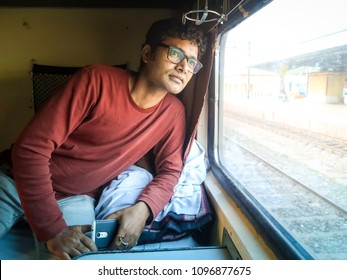 Handsome young indian man travel on train/ passenger wait to reach destination