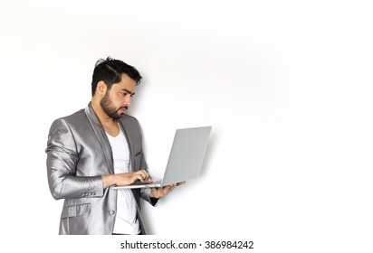 A handsome young Indian man working on laptop against a white background