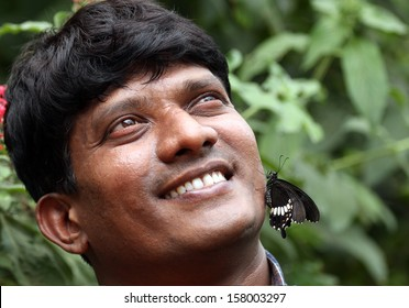 Handsome young Indian smiling with butterfly on face - concept of nature conservation. The photos shows a happy adult indian male with a just born black butterfly sitting on his face