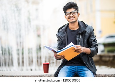 Handsome young indian student man read notebooks while standing on the street near fountain