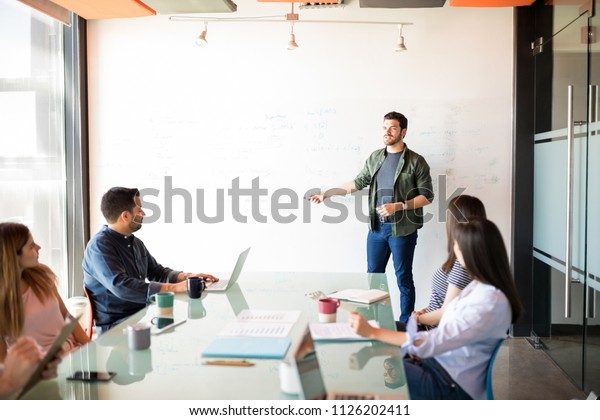 Красивый молодой латиноамериканский бизнесмен с презентацией группе людей в переговорном зале