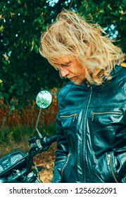 Handsome young long haired blond with a motorcycle in the countryside