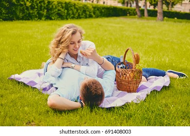 Handsome young male and blond female on a picnic in a summer park.