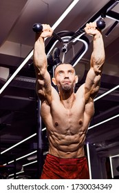 Schöner junger Bodybuilder im Fitnessraum. Grosser starker Mann während des Trainings im Fitnessraum. Mit großen Muskeln, Sportler, Trainer oder Instrukteur