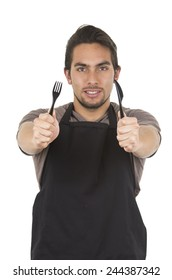 handsome young male chef wearing black apron holding fork and knife concept of hungry isolated on white
