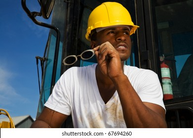 handsome young male construction worker wearing a hard hat, white t-shirt and jeans working beside his tractor rig