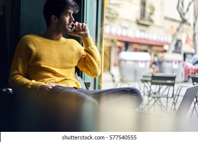 Handsome young male creative manager of company having phone conversation with colleague talking about working plan while being in trip on holiday using free wireless connection in urban coffee shop
