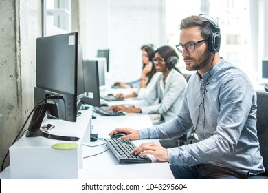 Handsome young male customer support executive working in office.