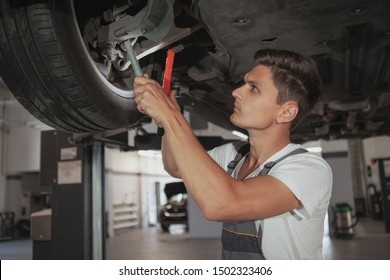 Handsome young male mechanic looking underneath the lifted automobile, holding a lamp. Auto technician examining wheels and underside of a car on the lift