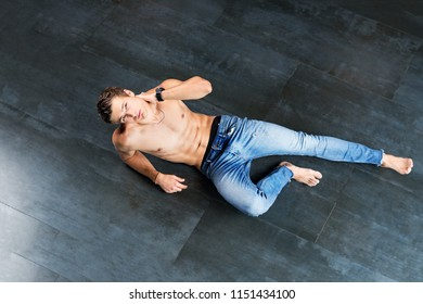 Handsome young male model on the floor shirtless at modern interior photostudio