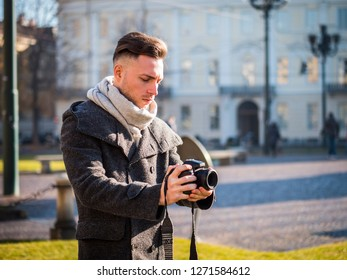 Handsome young male photographer filming video with professional videocamera hanging from his neck, outdoor in city street in Europe