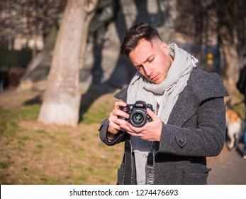 Handsome young male photographer or videomaker filming video footage with professional videocamera, outdoor in city park