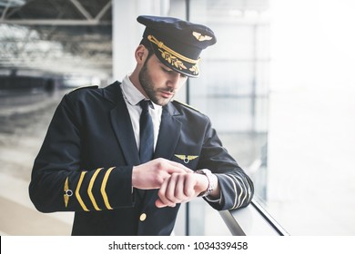 Handsome young male pilot is standing in the airport terminal and checking time.