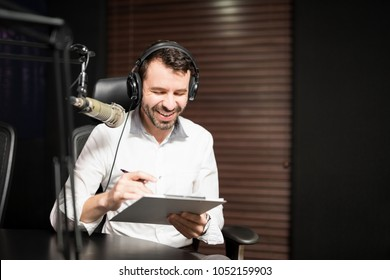 Handsome young male radio host with headphone sitting in front of a microphone interviewing a guest holding clipboard in studio